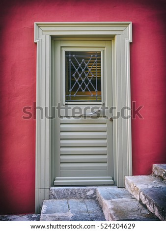 grey door on colorful fuchsia house wall, filtered