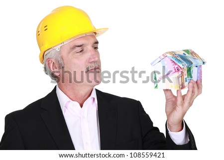 Grey-haired architect holding house made from bank notes - stock photo
