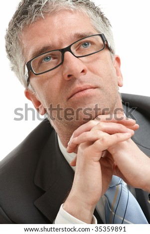 Grey haired businessman sitting and thinking. Low angle view. Isolated on white background.