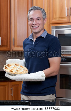 Grey haired man holding apple pie