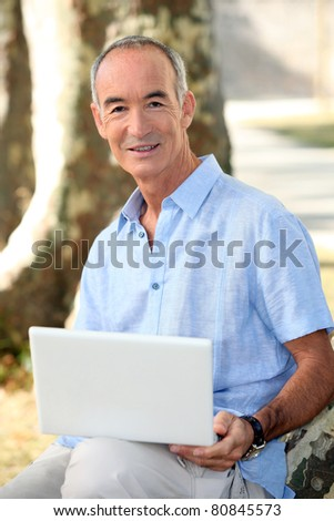 Grey haired man in park with laptop computer - stock photo