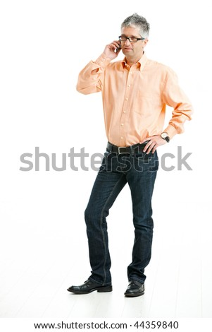 Grey haired man wearing jeans and orange shirt standing and talking on mobile phone. Isolated on white. - stock photo