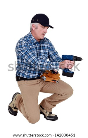 Grey haired man with drill - stock photo