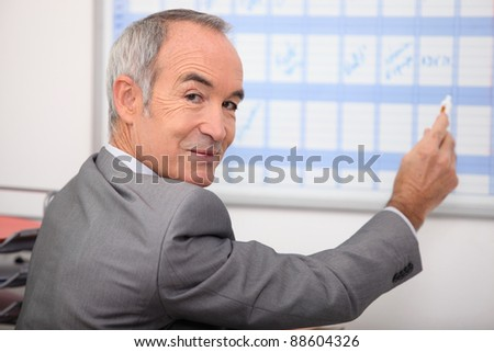 Grey haired man writing on calendar - stock photo