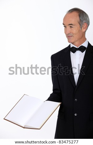 Grey haired restaurant worker presenting menu