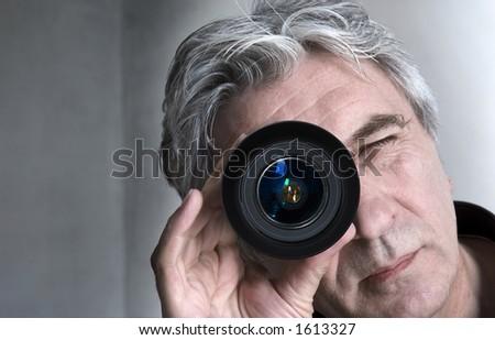 Grey-haired senior looking through a lens. - stock photo