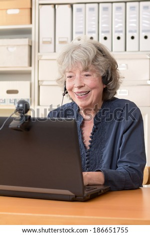 Grey haired woman sitting in front of her computer having a video chat, copy space - stock photo