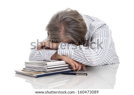 Grey haired woman sleeping on books - overworked isolated on white background - stock photo