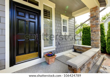 Grey house exterior with black door and stone wall. - stock photo