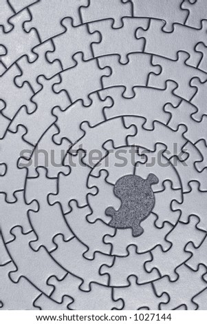 grey jigsaw with one missing piece - pieces fitting together in form of a spiral