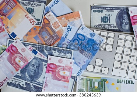grey keyboard littered with bills of different currencies (euros and dollars)