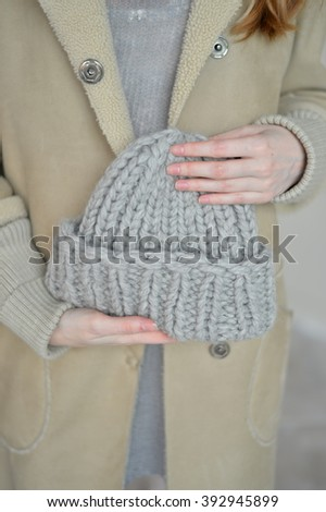 Grey knitted cap in her hand - stock photo