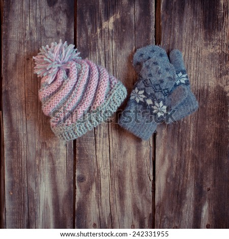 grey knitted winter gloves and hat on wooden boards - stock photo