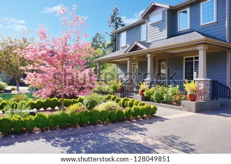Grey large luxury house  exterior with spring blooming pink trees. - stock photo