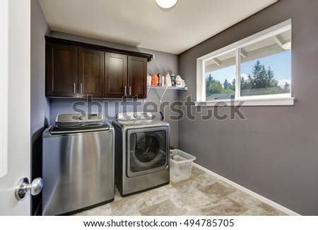 Grey laundry room with modern stainless steel washing machine and dryer, brown cabinets and  tile floor. Northwest, USA