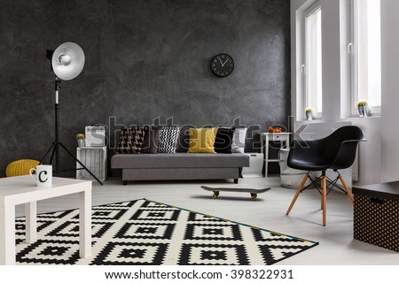 Grey living room with sofa, chair, standing lamp, small white table and black and white pattern carpet - stock photo