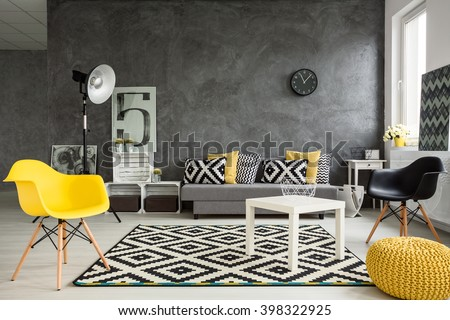 Grey living room with sofa, chairs, standing lamp, small table, yellow details and pattern decorations in black and white  - stock photo