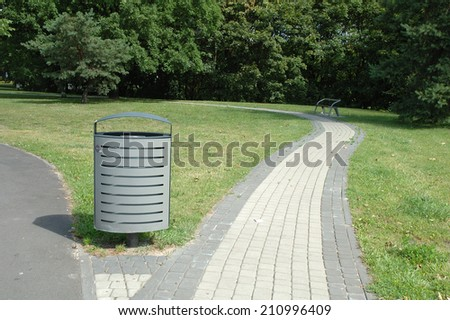 Grey metal dust bin nearby pavement in park in Poznan, Poland - stock photo