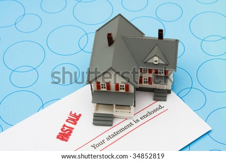 Grey model house with past due bills sitting on a blue background, foreclosure - stock photo