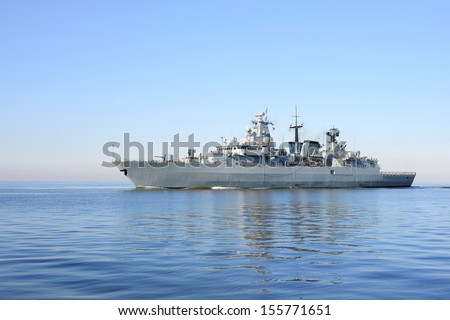 Grey modern warship sailing in still water  - stock photo
