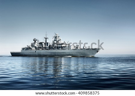 Grey modern warship sailing in still water