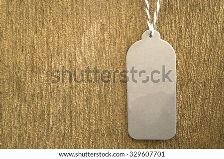 Grey paper price tag hanging on brown velvet with copy space for some text, advertise, promotion, sale  concept - stock photo