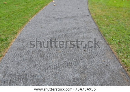 grey pebble path with tire tracks
