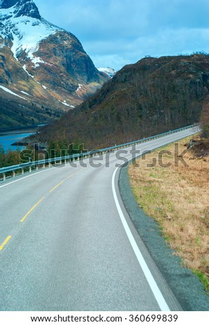 Grey road in Norvegian mountains in sunny day - stock photo