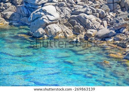 grey rocks and green plants by Capo Testa clear water, Sardinia - stock photo