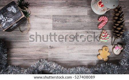 Grey rustic wooden table top with Christmas cookies and winter season accessories including a candle light, garland and a Christmas gift box