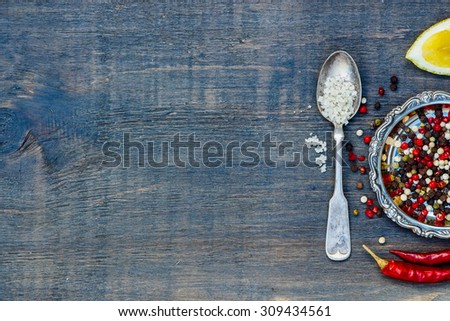 Grey salt and peppercorn mix on dark wooden background with space for text. Spices over wood. Cooking concept. - stock photo