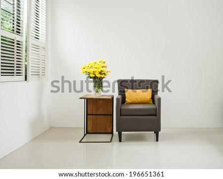 Grey sofa armchair in simple setting in front of lovered windows - stock photo