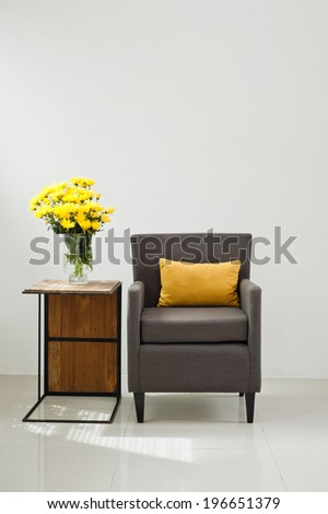 Grey sofa armchair in simple setting with yellow flowers - stock photo