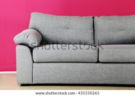 Grey sofa on a pink background, close up - stock photo