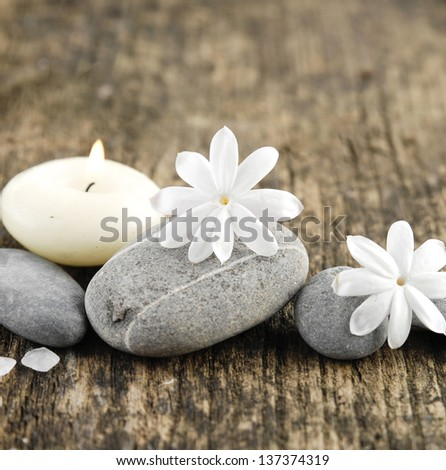 grey stones and white spring flower, candle on old wood - stock photo