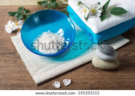 Grey stones, spring flower and sea salt in glass plate on the wood