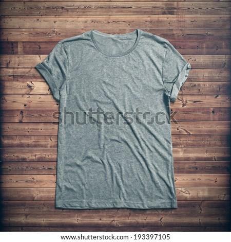 Grey t-shirt on wood background - stock photo