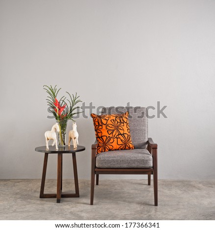 Grey upholstered chair in living room with flowers  - stock photo