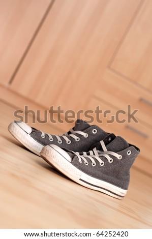 Grey vintage sneakers on the floor - stock photo