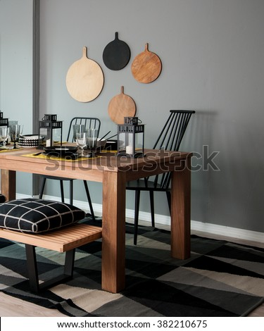 grey wall chopping board and wooden table black pillow black lantern with black white modern kitchen dining room corner - stock photo
