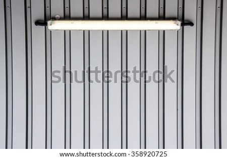 Grey wall of a container wall with a neon light - stock photo