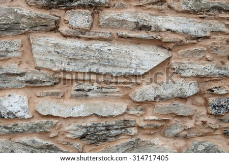 Grey wall of stone damaged by the passage of time - stock photo