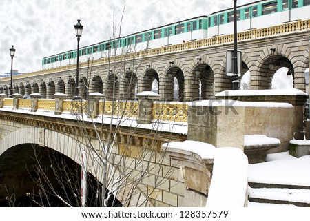 Grey winter day with snow laying everywhere, parisian metro train crossing the bridge over the Seine River. This picture makes me think about Hogwarts Express. / Paris metro train on the bridge - stock photo