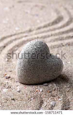 Grey zen stone in shape of heart, on sand background - stock photo