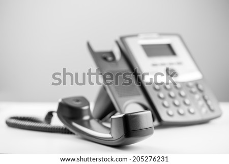 Greyscale image of a telephone receiver off the hook to either effectively block the line or waiting for a person to arrive to take the call. - stock photo