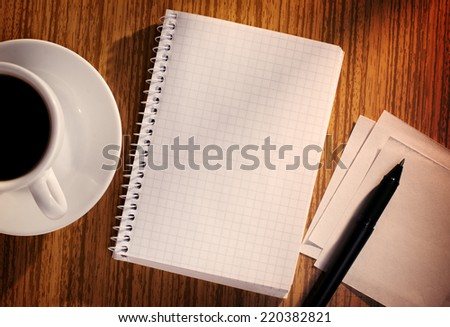 Grid Notebook and Pen with Cup of Coffee on Desk as seen from Above - stock photo