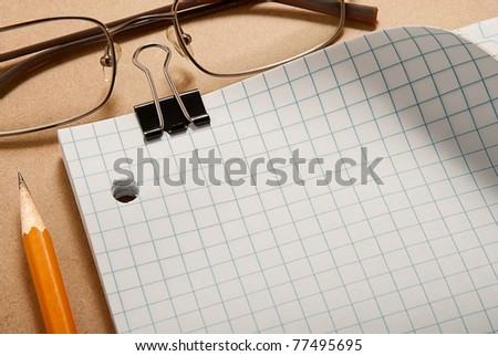 Grid paper with binder, glasses, and pencil over clip board background - stock photo