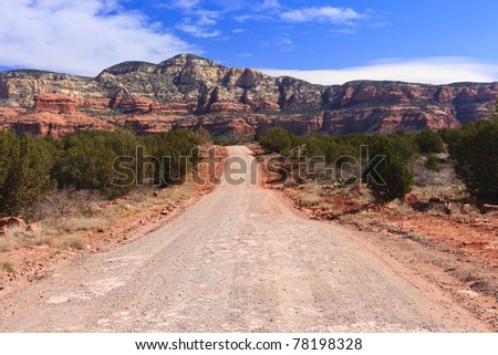Grid road through the desert with the red rocks of Sedona, Arizona in the distance