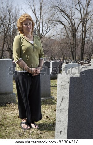 Grieving widow at the cemetary - stock photo