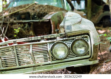 Grill and Twin Headlights on Old Rusted Car - stock photo